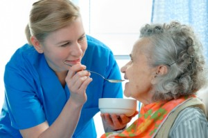 carer feeding senior some soupt